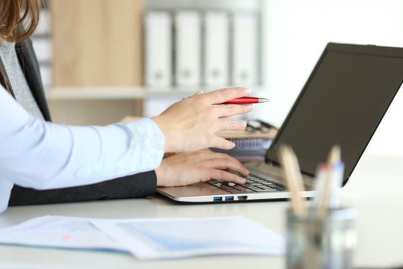 Kierownictwo wręcza pracującego z laptopem online przy biurem obraz stock
