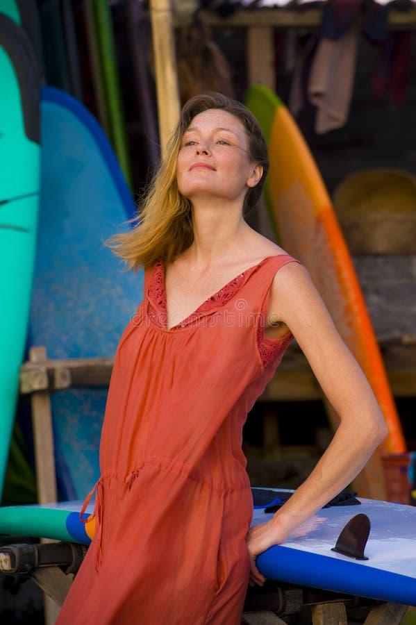 Kierowniczy i ramiona portret i relaksuję i rozochocony młoda blond kobieta uśmiecha się pozować z kolorowymi kipieli deskami obraz stock