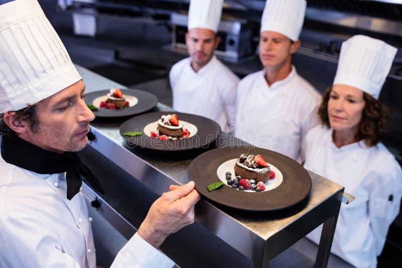 Kierowniczy szef kuchni sprawdza deserowych talerze dalej przy rozkaz stacją zdjęcia stock