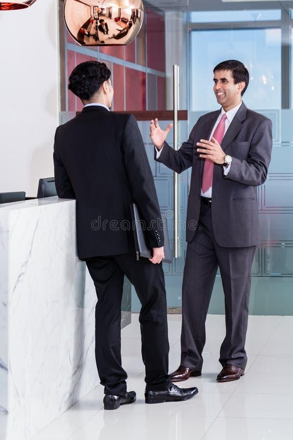 Kierownik i filia opiera przy frontowym biurkiem biuro obraz stock