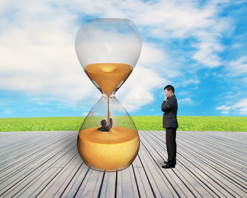 Kierownik nadzoruje biznesmena zalewającego w hourglass zdjęcia stock