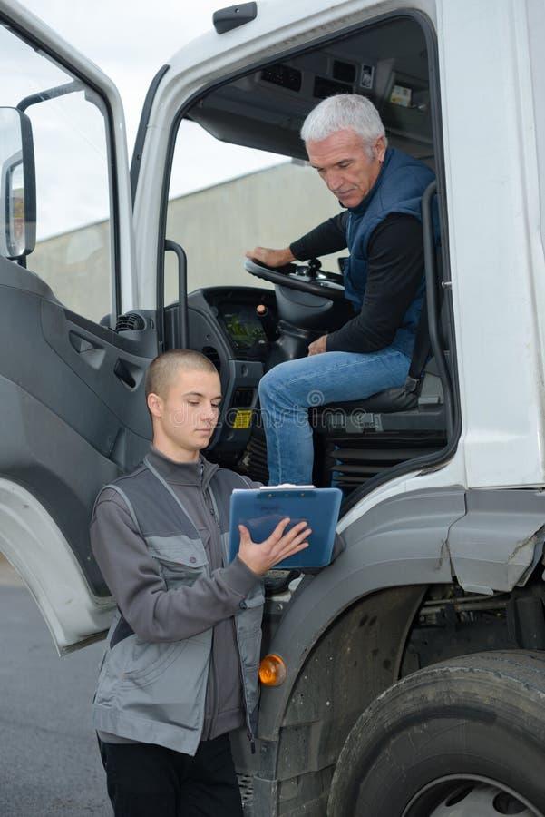 Kierownik opowiada kierowca ciężarówki w magazynie obrazy stock