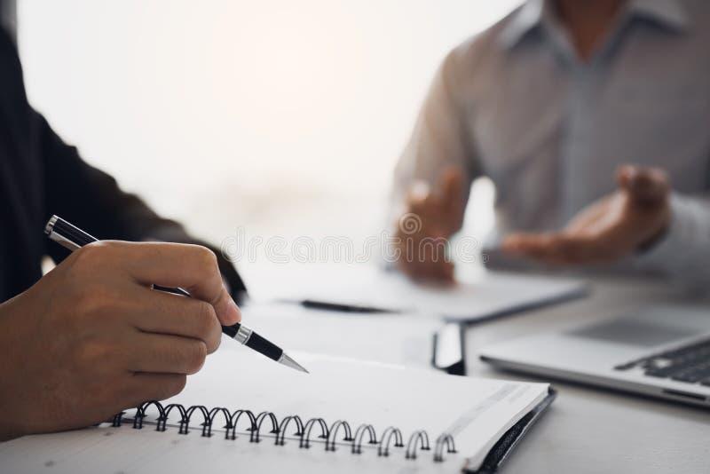 Kierownik pisze informacji osobistej pracownicy które przychodzą stosować dla prac w notatniku obraz stock