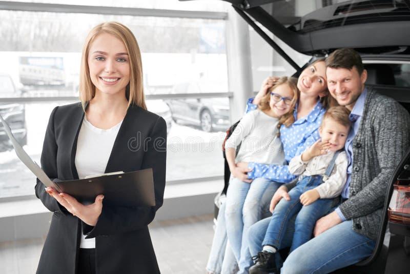 Kierownik przedstawicielstwo firmy samochodowej i szczęśliwy rodzinny pozować, ono uśmiecha się obrazy royalty free