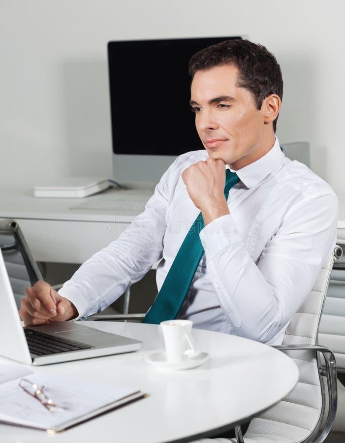 Kierownik z laptopem przy biurowym biurkiem zdjęcia stock