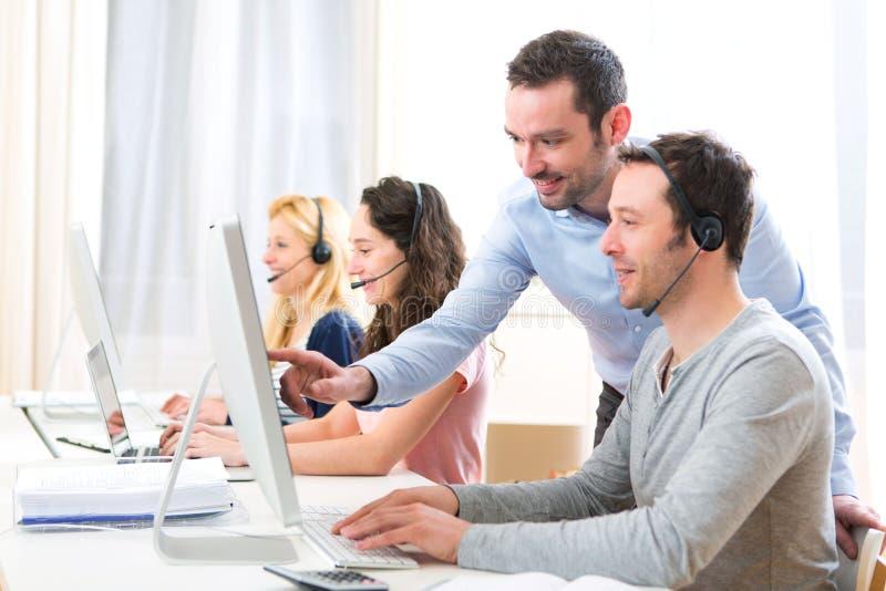 Kierownika trenować młodzi atrakcyjni ludzie na komputerze obraz stock