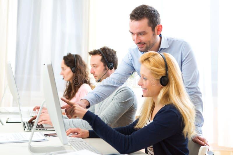 Kierownika trenować młodzi atrakcyjni ludzie na komputerze obrazy stock