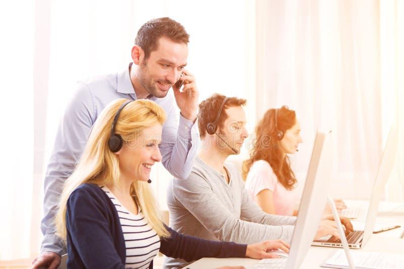 Kierownika trenować młodzi atrakcyjni ludzie na komputerze zdjęcia royalty free