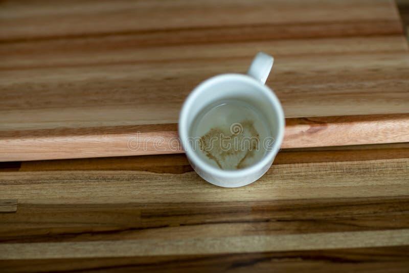 Kierowy kształt wśrodku filiżanka kawy Filiżanka kawy z sercem Wśrodku filiżanki brązu Drewnianego tła obraz royalty free