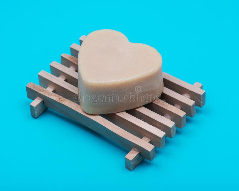 Kierowy kształtny kózki mleka mydło na naturalnym drewnianym naczyniu oddzielał na błękicie zdjęcie stock