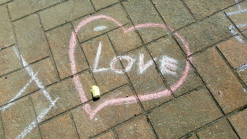 Kierowy nakreślenie z tekst miłością - kredowy rysunek na kamiennym bruku obrazy royalty free