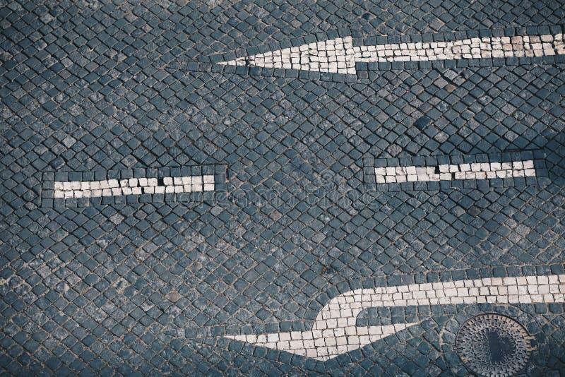 Kierunku znak uliczny na handmade kamiennym bruku w Lisbon i strzała - Tradycyjny Portugalski handmade mozaiki tło zdjęcia stock