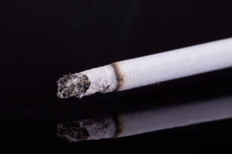 Kies brandende die sigaret met as uit op zwarte achtergrond wordt geïsoleerd royalty-vrije stock foto's