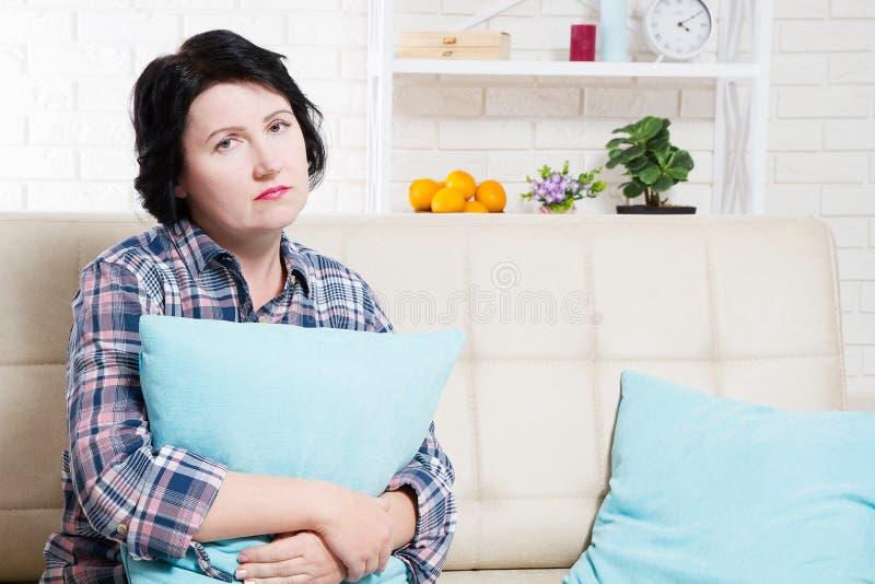 Kies mooie vrouw droevig en eenzaam in slaapkamerzitting op bank en het koesteren van een hoofdkussen uit royalty-vrije stock foto's