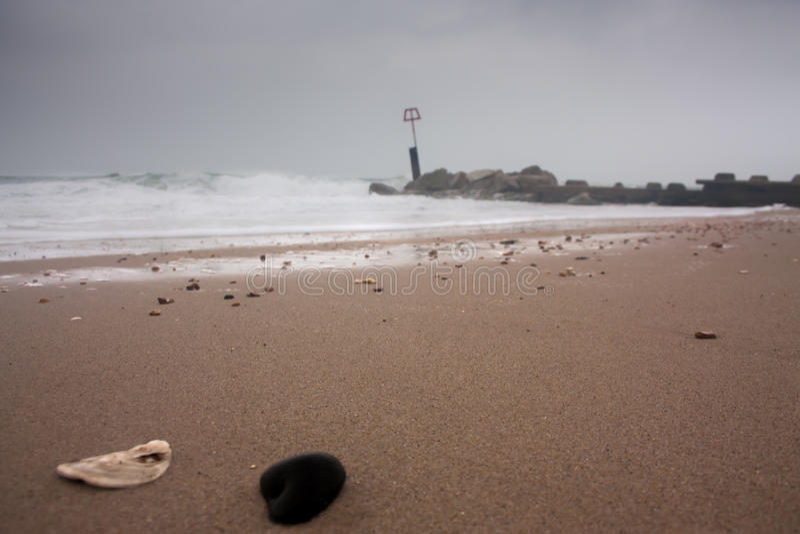 Kiesel auf bewölktem und windigem Strand stockbilder