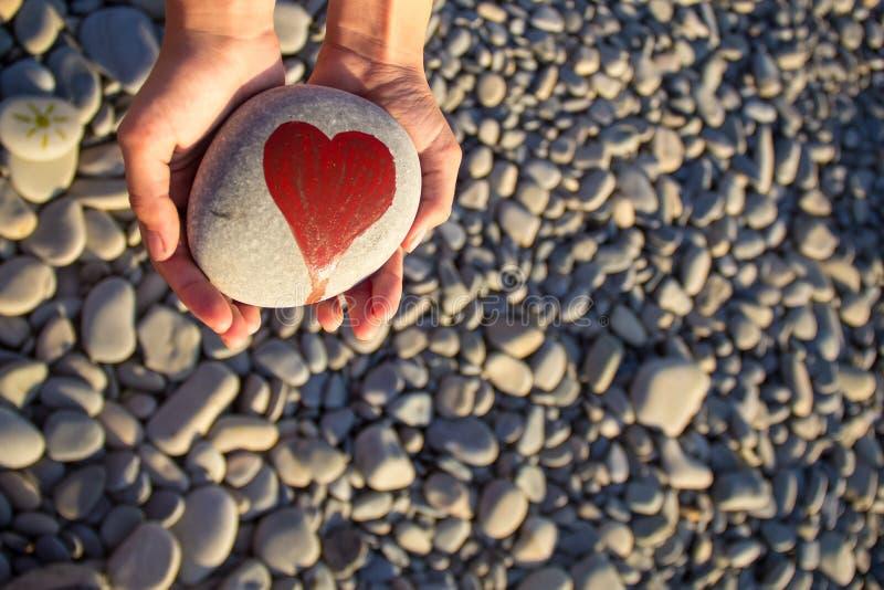 Kiesel mit einem gemalten Herzen in den Händen eines Kindes auf dem Hintergrund von einem Pebble Beach lizenzfreies stockbild