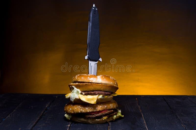 Kieszeniowy nóż w hamburgerze Falcowanie hamburger i nóż obraz royalty free