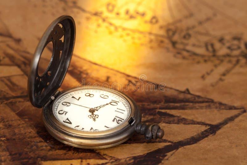 Kieszeniowy zegarek na starym mapy tle, rocznika styl fotografia royalty free