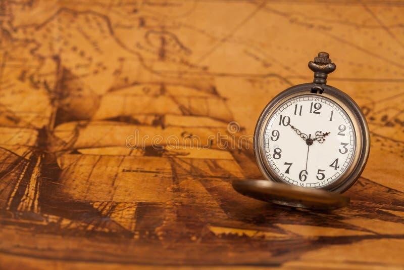 Kieszeniowy zegarek na starym mapy tle, rocznika styl obrazy royalty free