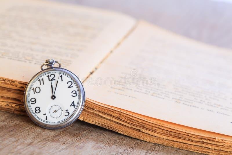 Kieszeniowy zegarek obok książki zdjęcie stock