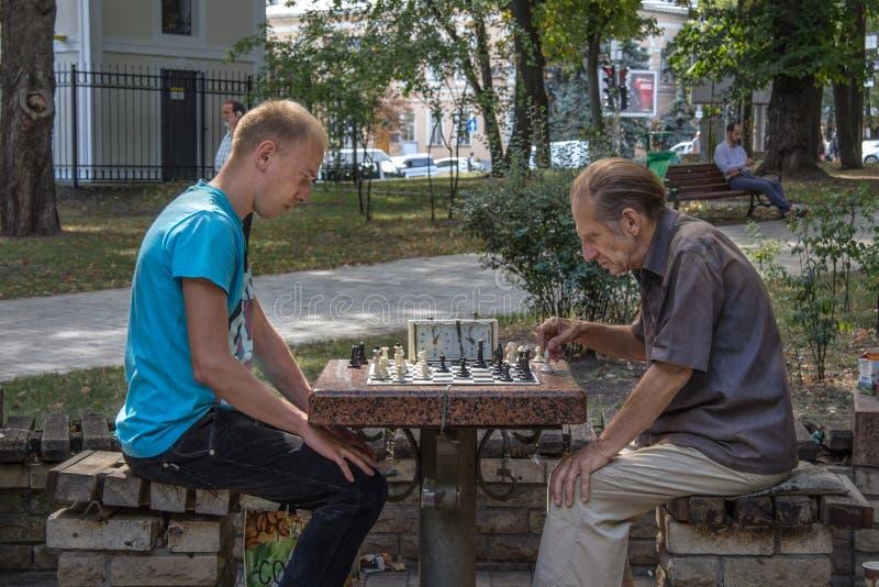 KIEV, DE OEKRAÏNE - AUGUSTUS 17, 2015: Oude en jonge mensen die schaak in Taras Shevchenko Park, Kiev, hoofdstad spelen van de Oe stock foto's