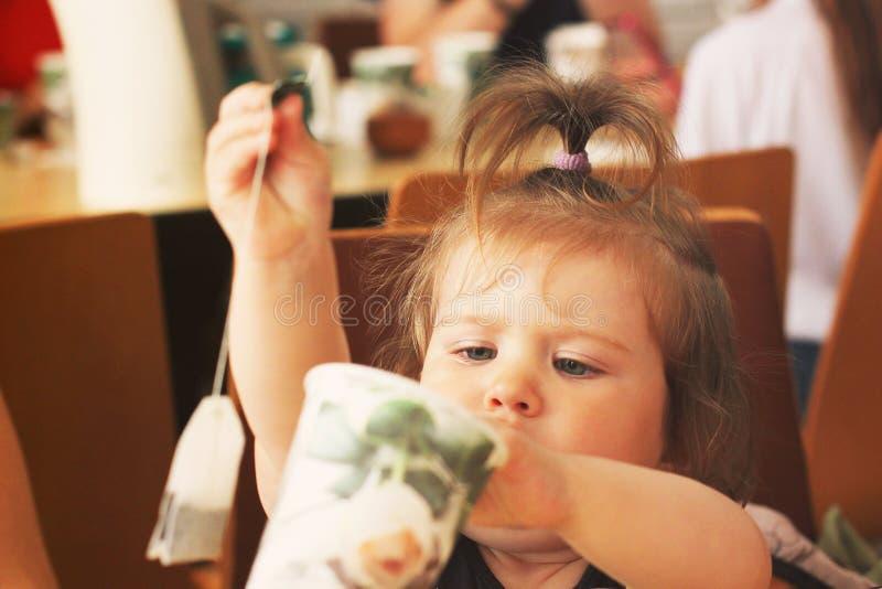 Kiev, de Oekraïne - Februari 28, 2018: Een klein meisje zit bij de lijst en maakt thee royalty-vrije stock foto