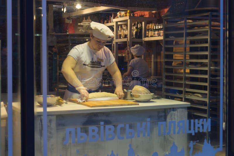 Kiev, de Oekraïne - Februari 25, 2018: Pannekoeken van de mensen de kok gekookte aardappel in een winkelvenster royalty-vrije stock foto