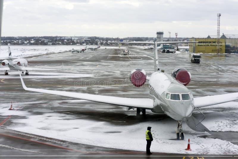 Kiev, de Oekraïne, Februari 2019 Vliegtuigen, de baan, de arbeiders - de gebruikelijke wijze van verrichting van de luchthaven Ki stock foto's