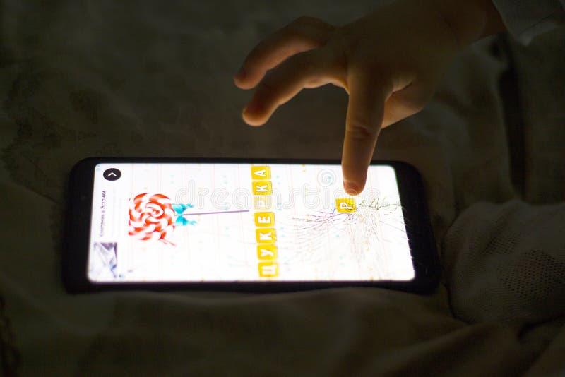 Kiev, de Oekra?ne 05 16 het meisje van 2019 leert om woorden in de toepassing voor kinderen op een mobiel Illustratief Hoofdartik stock afbeeldingen