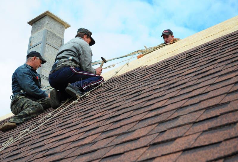 KIEV - DE OEKRAÏNE, JANUARI - 11, 2017: Dakwerkbouw De dakwerkcontractanten installeren Nieuw Huisdakwerk met Asphalt Shingles stock foto