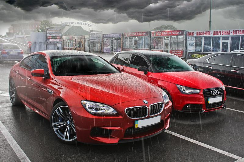 Kiev, de Oekraïne 20 mei, 2014, Twee rode auto's in de regen BMW M6 en Audi A3 royalty-vrije stock afbeelding