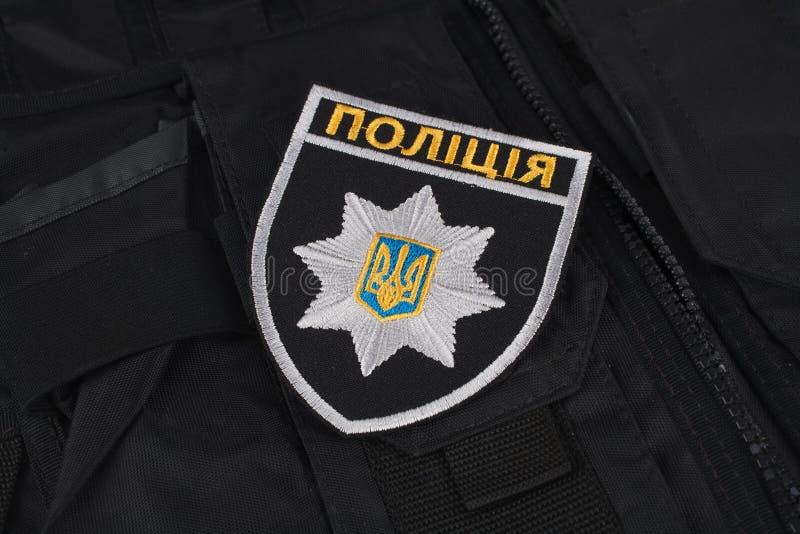 KIEV, DE OEKRAÏNE - NOVEMBER 22, 2016 Flard en kenteken van de Nationale Politie van de Oekraïne op zwarte eenvormige achtergrond stock fotografie