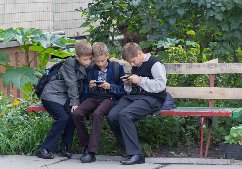 Kiev, de Oekraïne - September 10, 2015: Studenten die die op de bank zitten met behulp van smartphones wordt gespeeld stock afbeelding