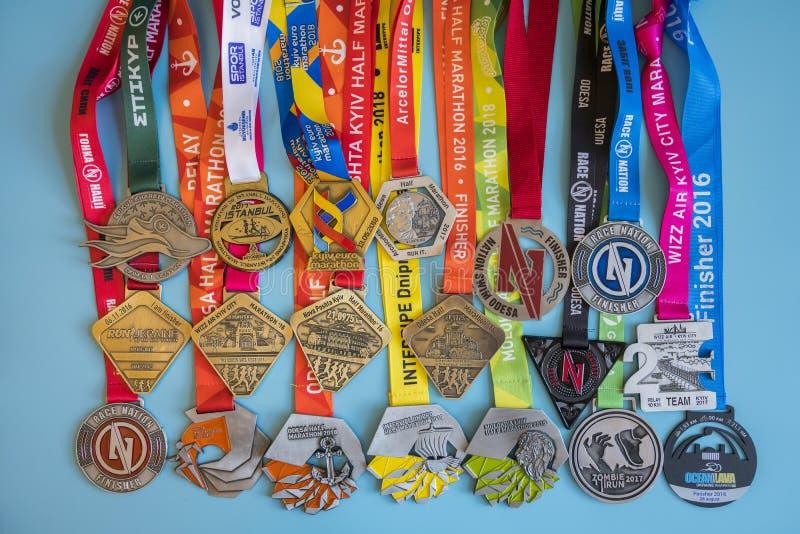 Kiev, de Oekraïne 2 september 2018 Vele verschillende sportenmedailles op een blauwe achtergrond Medailles voor halve marathon, m stock foto