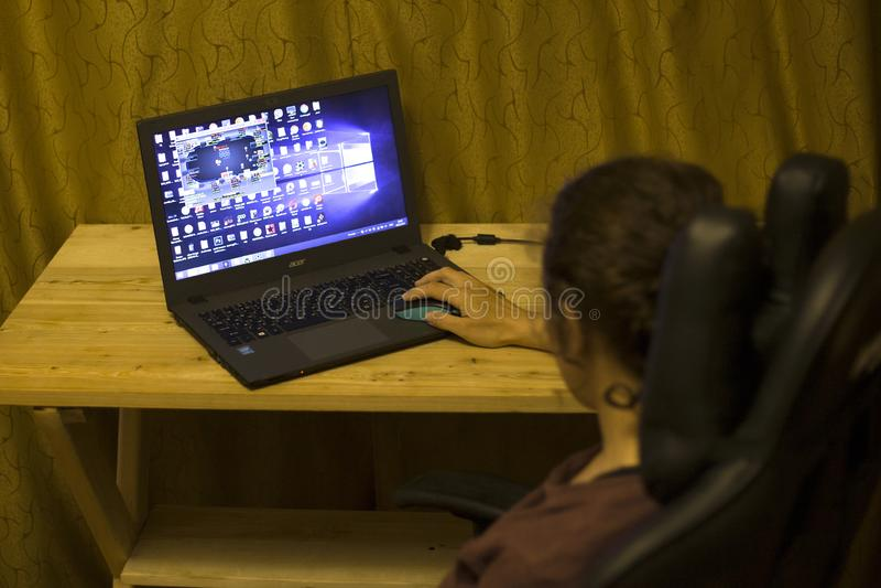 Kiev, de Oekra?ne 05 12 2019: meisje die online pook voor laptop Illustratief Hoofdartikel spelen stock foto
