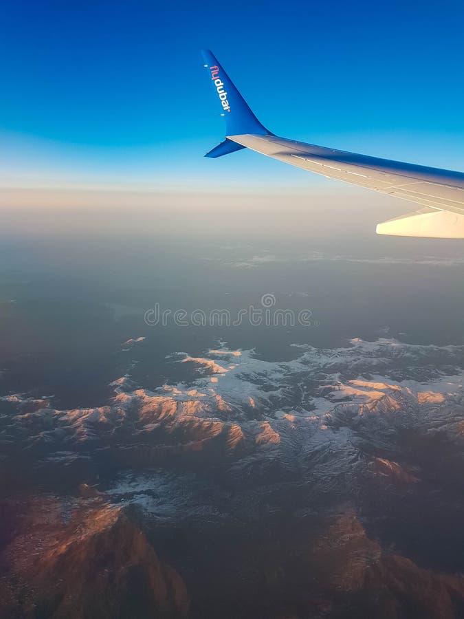 Kiev - Dubaï, novembre 2018 : Vue des montagnes de la fenêtre d'avion de flydubai pendant le vol au coucher du soleil photos libres de droits