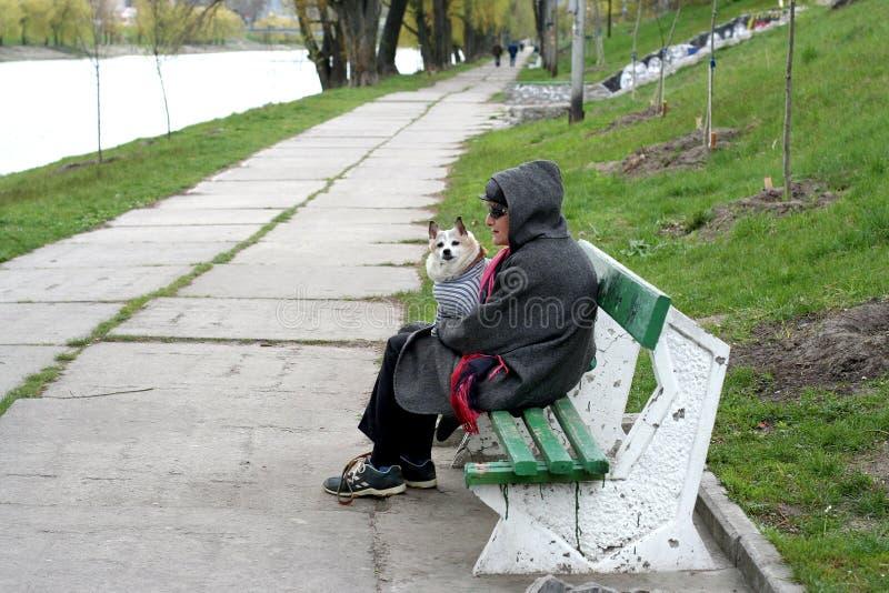 kiev l'ukraine 21 04 2007 Une femme s'assied sur le banc et tient un chien sur ses mains photo stock