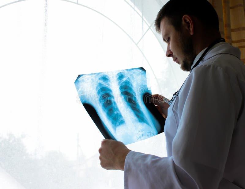 Kiev region, Ukraina - Oktober 12 2016: Dr terapeut i ett kontor som ser röntgenstrålen de tålmodiga lungorna för ` s royaltyfria foton