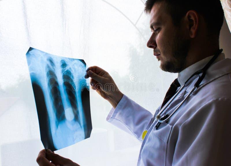 Kiev region, Ukraina - Oktober 12 2016: Dr terapeut i ett kontor som ser röntgenstrålen de tålmodiga lungorna för ` s royaltyfri bild