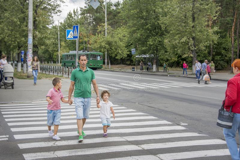 Kiev. In summer, at the pedestrian crossing, the father and children cross the road. royalty free stock photo