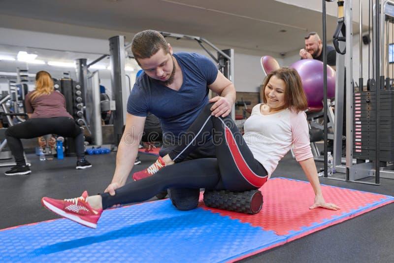 Kiev uA, 28-03-2019 Donna matura che fa gli esercizi di sport con l'istruttore personale alla palestra Istruttore maschio che ass fotografia stock