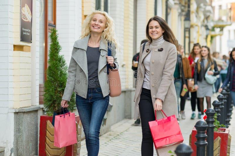 Kiev UA, 14-10-2018 Estilo urbano, dos mujeres de moda sonrientes jovenes que caminan a lo largo de una calle con los bolsos de c fotos de archivo libres de regalías