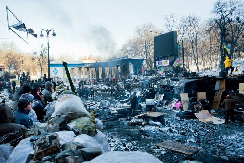 KIEV, UCRÂNIA: Cidadãos comuns que olham sobre barricadas contra as forças especiais na rua destruída nevado fotos de stock royalty free