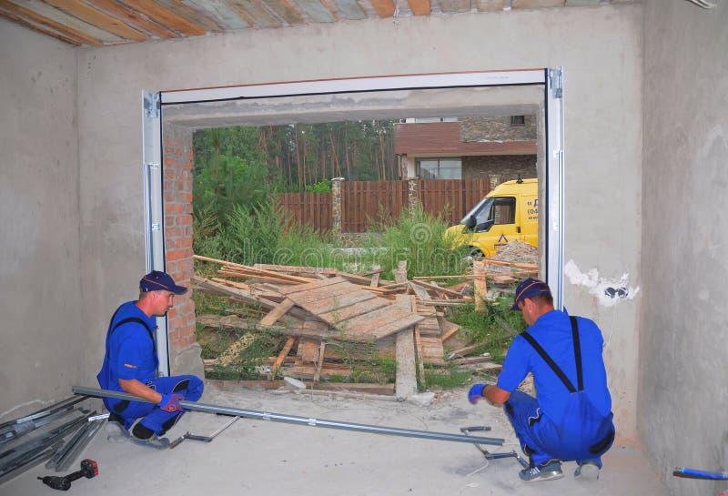KIEV, UCRÂNIA - 13 DE JULHO DE 2016: Contratantes que instalam a porta da garagem imagens de stock royalty free