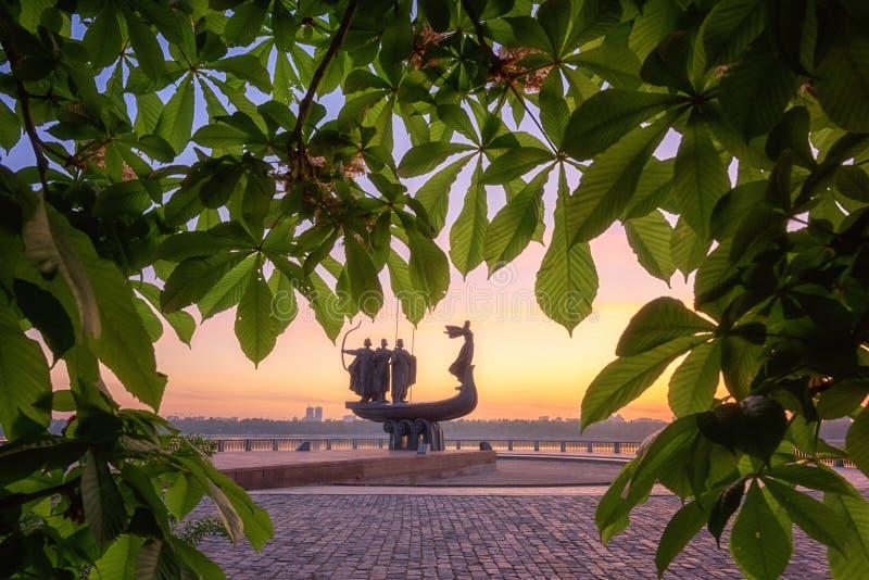 Kiev, Ucrânia - 5 de maio de 2018: Fundadores do monumento de Kiev no nascer do sol através da castanha de florescência, opinião  foto de stock
