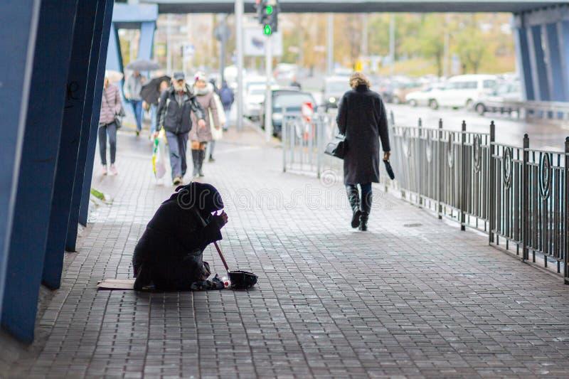 Kiev, Ucrânia - 24 de outubro de 2018: A mulher adulta miserável senta-se no passeio cercado imagem de stock royalty free