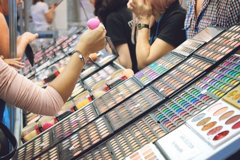 Kiev, Ucrânia 19 de setembro de 2018: A jovem mulher escolhe cosméticos decorativos no suporte da loja da beleza durante a mostra foto de stock