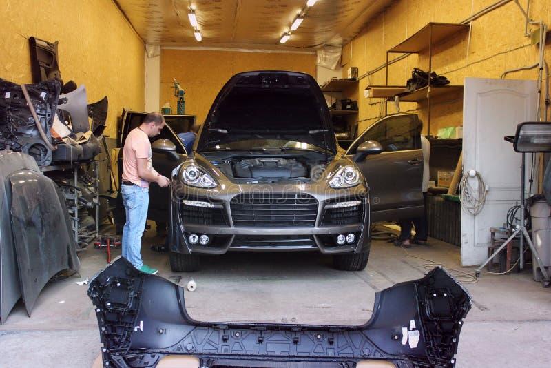 Kiev, Ucrânia - 2 de setembro de 2016: Serviço do carro Mestres no reparo Porsche Cayenne da garagem imagens de stock