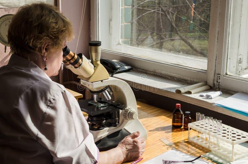 KIEV, UCRÂNIA, MARCN, 2017: O assistente de laboratório conduz o exame médico com a ajuda do microscópio, Kiev, Ucrânia foto de stock royalty free