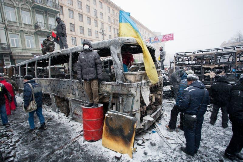 KIEV, UCRÂNIA: Os guardiães civis esperam o ataque dos polícias nas barricadas da rua de ocupação da neve durante o motim do inver imagem de stock